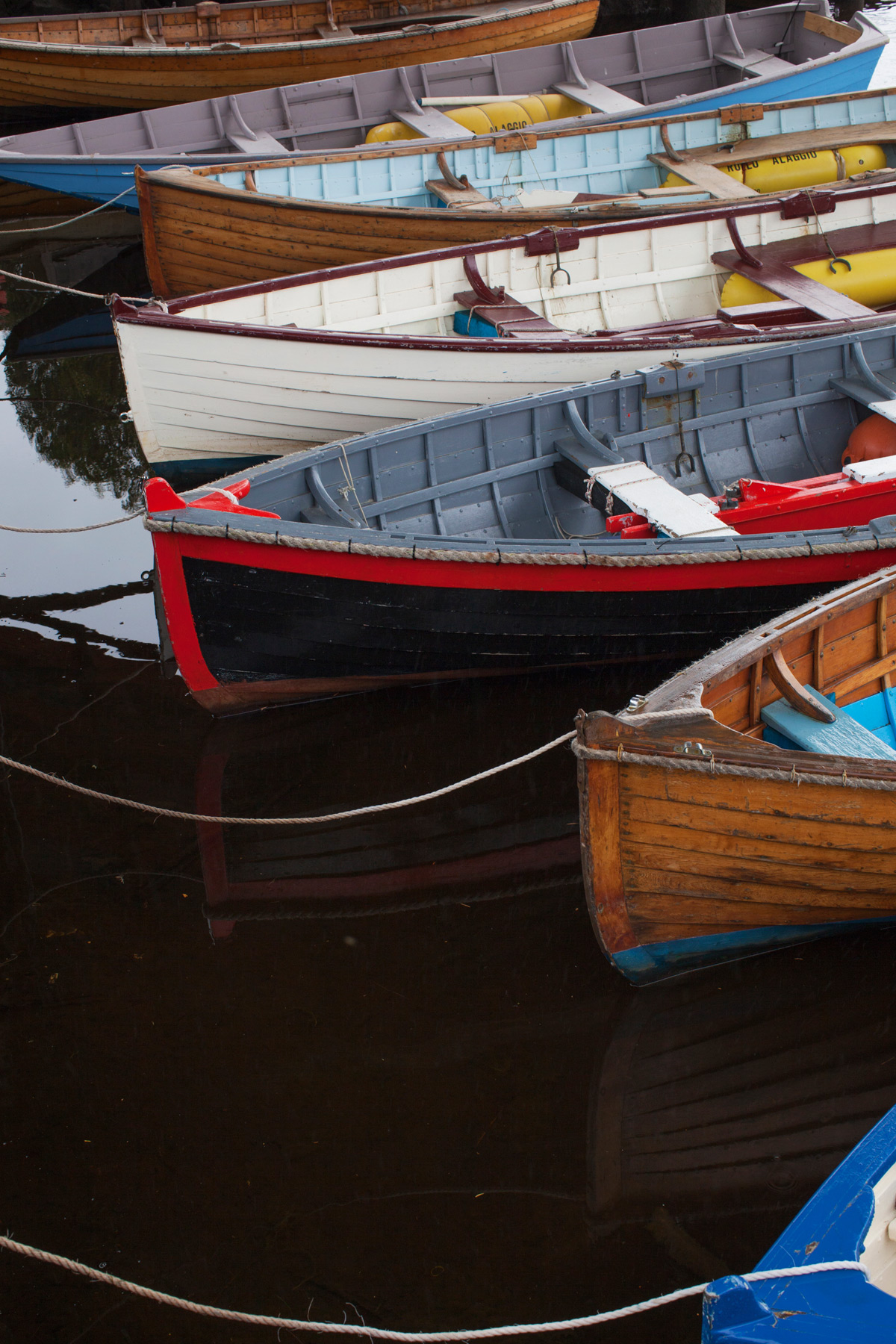 A row of coloured wooden boats on the water