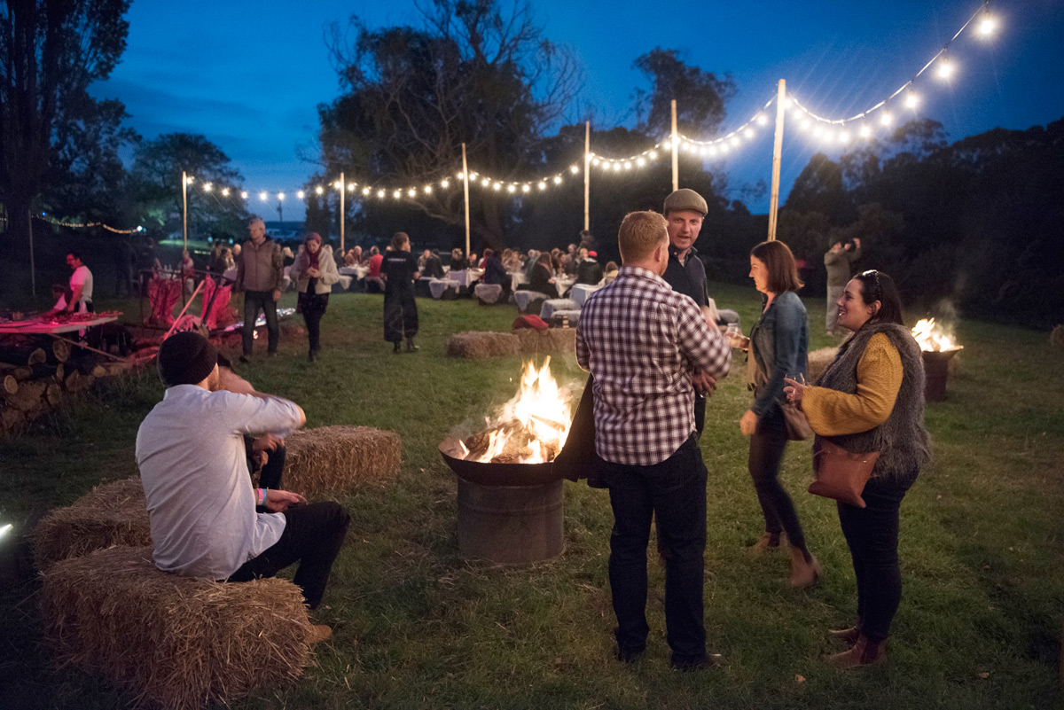 People standing around talking near a fire pit with colourful fairy lights in the background